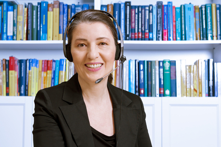 Friendly smiling middle aged woman with headset and black blazer in an office with lots of books, lawyer or accountant, online legal or tax advice