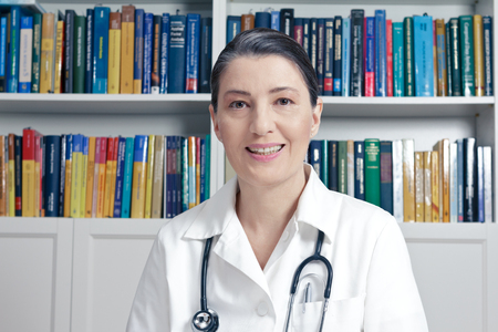 Friendly doctor with stethoscope in front of a lot of books in her surgery office talking to a patient, frontal view, medical consultation concept