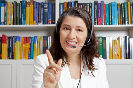 additional training: Friendly smiling mature teacher with headphones and white blazer in front of a bookshelf in an office, teaching via an online video call, telelearning