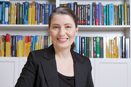 Friendly smiling mature woman with black blazer in an office with lots of books, professor, teacher, translator, lawyer, accountant or businesswoman Banque d'images