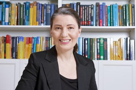 Vriendelijk lachende volwassen vrouw met zwarte blazer in een kantoor met veel boeken, professor, leraar, vertaler, advocaat, accountant of zakenvrouw
