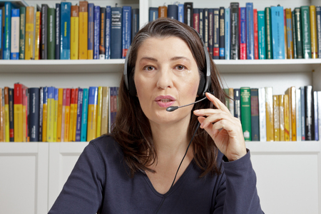 Friendly middle aged woman with blue t-shirt and headset in an office with lots of books having an live video call via the internet, telelearning, e-education Stock Photo
