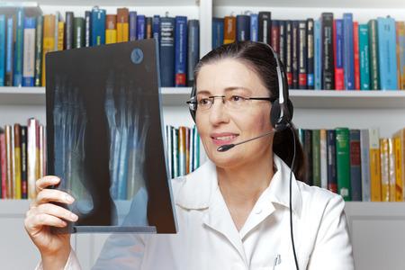 Vrouwelijke arts of radioloog met hoofdtelefoon en een röntgenstraal van een voet in hand zoals die door een webcam, telehealthconcept wordt gezien