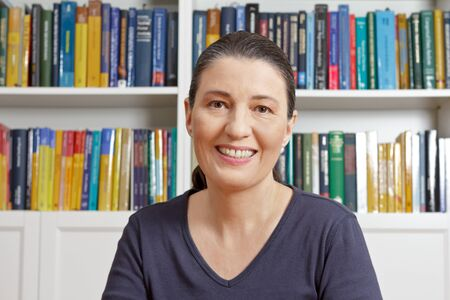 Happy middle aged woman with blue t-shirt in front of lots of books, having an live video chat with her family or onlne dating Stock Photo