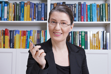 Friendly middle aged woman with black blazer in an office with lots of books explaining something during an online lesson, e-learning or e-education concept