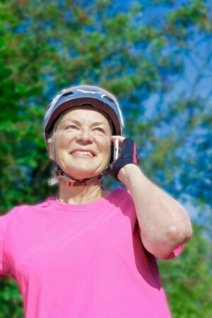 Senior woman in front of bushes and blue sky in summer sun with pink sport shirt, cycling gloves and helmet talking to someone with her mobile phone