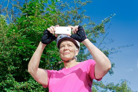 Senior woman in front of bushes and blue sky in summer sun with pink sport shirt, cycling gloves and helmet taking a photo with her smartphone
