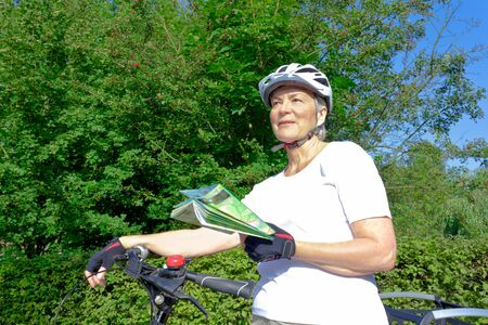 Senior woman outdoors in the summer sun with bicycle helmet, gloves, white t-shirt and map, looking for the right course for her recreational trip
