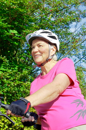 Smiling senior woman with white helmet and protective gloves holding her bicycle on a sunny summers day, green bushes in the background Stock Photo