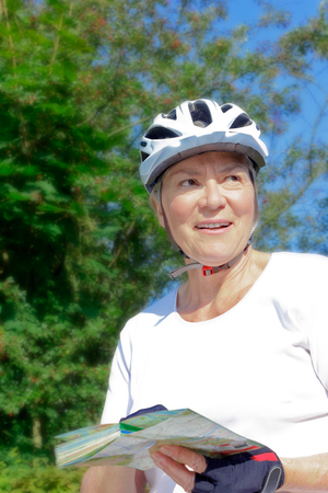 Senior woman outdoors in the summer sun with bicycle helmet, gloves, white t-shirt and map, enjoying the view, active retirement concept Stock Photo