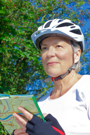 Senior woman outdoors in the summer sun with bicycle helmet, protective gloves, white t-shirt and map, looking for her position and orientation
