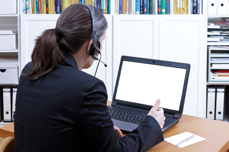 background skype: Female professional with headset in front of a laptop talking to someone during an online video call, empty screen, copy and text space