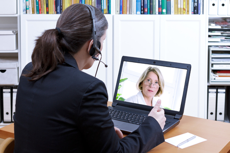 Female tax adviser with headset in front of a laptop giving online financial advice to an elderly client, video call concept, copy space Banque d'images
