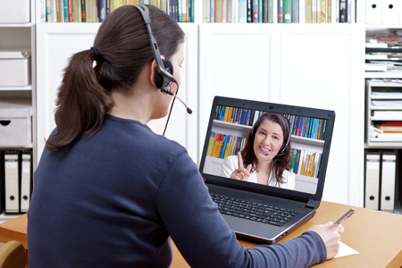 Woman with pen and paper and a headset in front of her laptop making a video call with her friendly tutor, text space