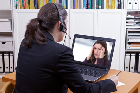 Woman with headset in front of her laptop writing something on a paper while making a live video call with a patient or client, copy space Banque d'images
