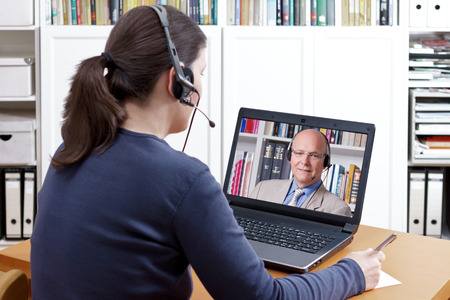 Woman with pen and paper and a headset in front of her laptop making a video call with her friendly professor, text space Standard-Bild