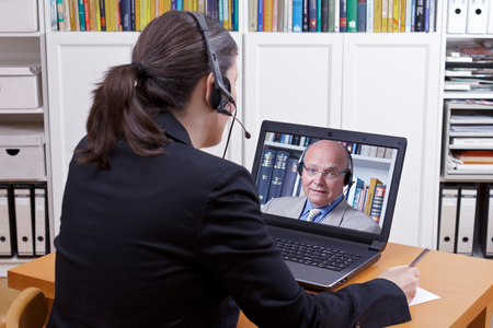Woman with headset in front of her laptop writing something on a paper while making a live video call with a client or colleague, copy space