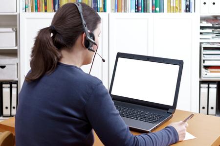 Vrouw met pen en document en een hoofdtelefoon voor haar laptop die een online vraag, het geïsoleerde witte computerscherm maken, exemplaarruimte Stockfoto