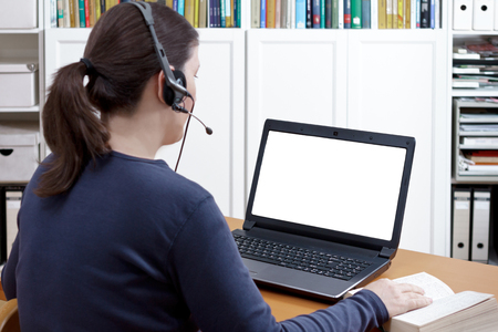 Woman with headset and book at her desk in front of her laptop having an online video call, isolated computer monitor, copy space Banque d'images