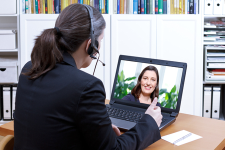 Female teacher with headset in front of a laptop on her desk giving a private online lesson to an adult student, e-learning concept, copy space Stock Photo