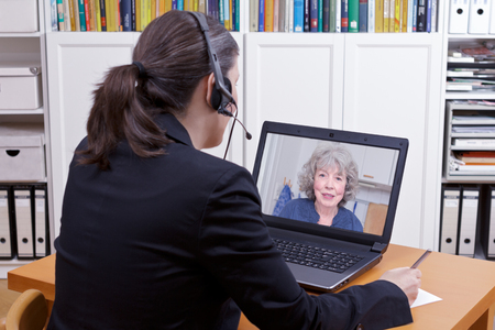 Female lawyer with headset in front of her laptop writing something on a paper while having a live video chat with an elderly client, copy space