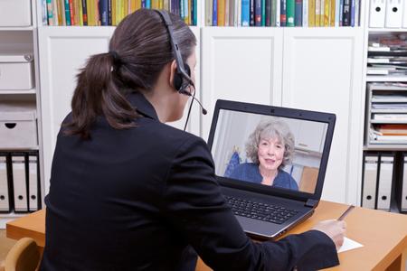Vrouwelijke advocaat met hoofdtelefoon voor haar laptop wat iets op een papier schrijft terwijl ze live videochat heeft met een oudere client, kopieer ruimte Stockfoto