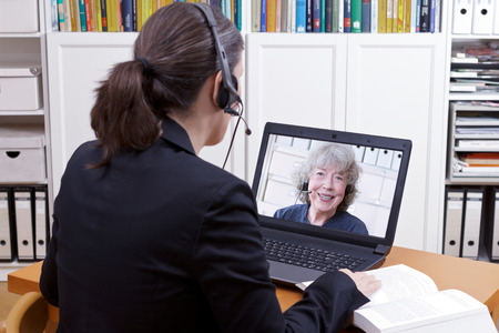 Woman with headset in front of her laptop and a book making an online video chat with a senior female client or mandator, text space