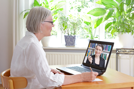 Senior woman at home in front of her laptop making notes during watching an online video of tax advice by a female accountant