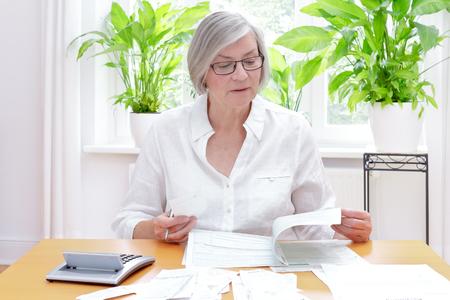 Hogere Duitse vrouw thuis met een calculator en veel rekeningen en ontvangstbewijzen, die de gedrukte vormen van de jaarlijkse belastingsverklaring invullen
