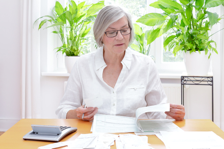 Senior german woman at home with a calculator and lots of bills and receipts, filling out the printed forms of the annual tax declaration Foto de archivo
