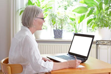 Hogere vrouw thuis voor haar laptop die nota's, online raad of e-lerend conceptmalplaatje, het witte scherm, exemplaarruimte nemen