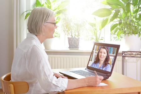수석 여자 집 여성 온라인 교사, 전자 학습 개념에 의해 온라인 영어 수업을 보는 동안 노트를 만드는 그녀의 노트북의 앞에 집