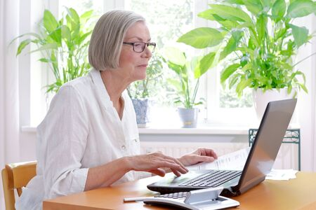 Relaxed senior woman at home with a calculator and lots of receipts in front of her laptop making her annual tax declaration Stock Photo