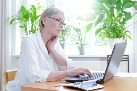 negatively: Senior woman in her living room staring annoyed at the screen of her laptop,computer or financial problems