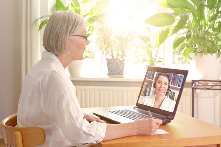 Senior woman in her sunny living room in front of a laptop making notes during watching an online advice video by a female therapist Standard-Bild