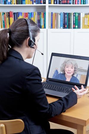 Vrouwelijke psycholoog met hoofdtelefoon in haar kantoor voor haar computer, praten met een senior vrouw tijdens een live video call of chat, online counseling sessie sjabloon