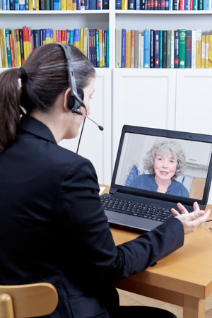 Female psychologist with headset in her office in front of her computer, talking to a senior woman during a live video call or chat, online counseling session template