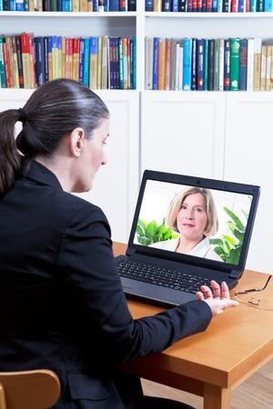 Achteraanzicht van een zakenvrouw in haar kantoor voor haar laptop, met een videogesprek met haar arts via internet, telemedicine of telehealth concept