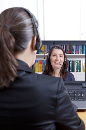 Member of the human resources department in her office with computer and headset, carrying out an online job interview with a young female applicant