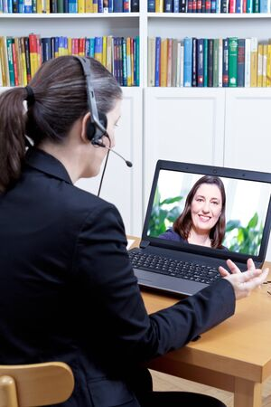 Head of the human resources department with headset in her office in front of her computer, carrying out a video call job interview with a young female applicant
