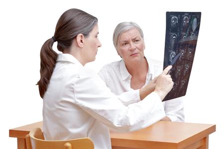 Vrouwelijke midden oude arts die haar hogere patiënt een mri van haar die hoofd toont, op witte achtergrond wordt geïsoleerd