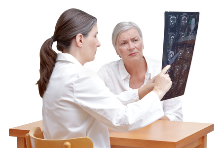 Female middle aged doctor showing her senior patient an mri of her head, isolated on white background