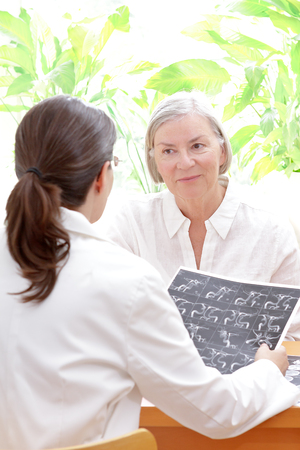 Female doctor with an mra image or angiogram discussing with a senior patient her risk to suffer an apoplectic stroke, copy space Stock Photo