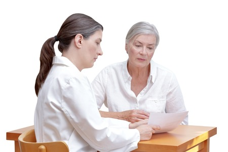Female doctor showing her senior patient a paper bill or check, listing the costs of the medical treatment, isolated on white background