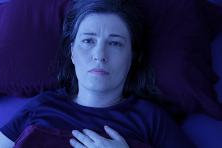 Middle aged woman lying awake in her bed at night because of insomnia, stress, fears, nightmares or restless leg syndrome