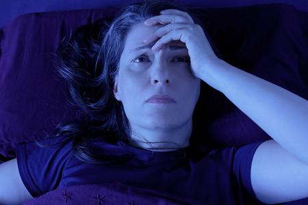 Vrouw van middelbare leeftijd die 's nachts wakker ligt in haar bed vanwege slapeloosheid, stress, angsten, nachtmerries of ziekten zoals fibromyalgie Stockfoto