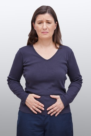 Middle aged woman with a pained expression on her face pressing her hands on her belly, bellyache caused by food intolerance