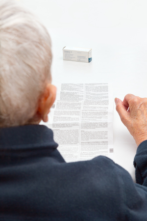 old woman unable to read drug package leaflet Archivio Fotografico