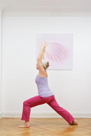 Senior woman yoga exercise warrior Banco de Imagens
