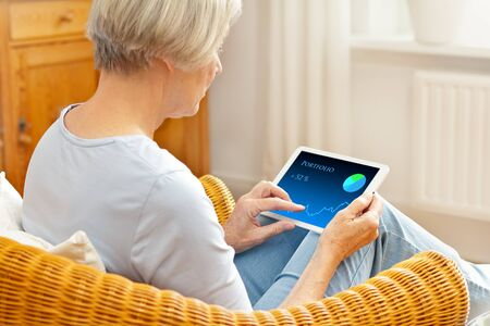 Senior woman in her living room checking her investment portfolio on a tablet computer. Фото со стока - 137955093